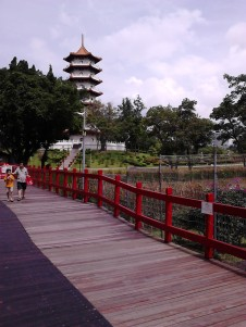 Mom and son walking on the bridge with the pagoda at the background