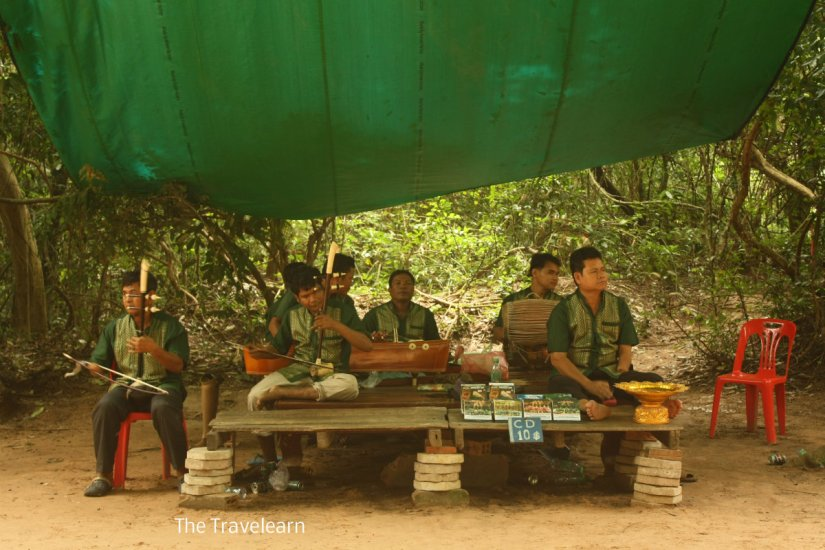 Cambodian traditional music player in front of Ta Prohm gate