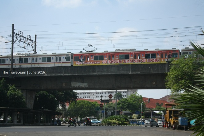 A commuter train is running on the elevated track near Monumen Nasional